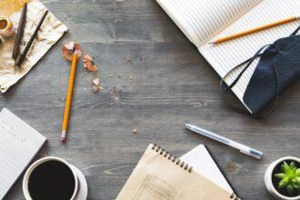 Escrivaninha de escritor com papéis, lápis, caderno e café