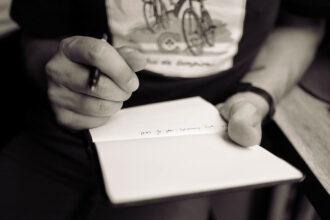 Pessoa anotando texto em um bloco em branco