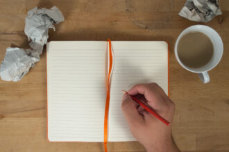 Escritor escrevendo no caderno em branco