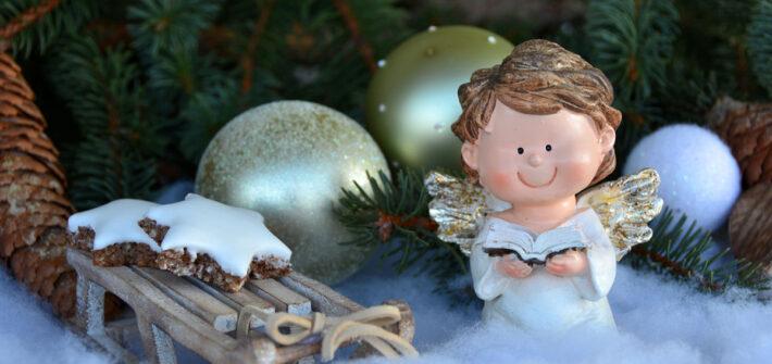 Anjo de Natal lendo livro debaixo da árvore de natal
