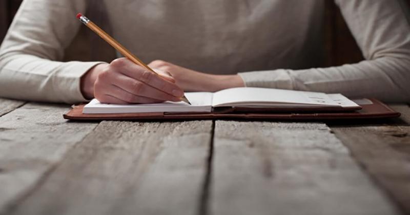 Homem escrevendo ficção em um caderno na mesa