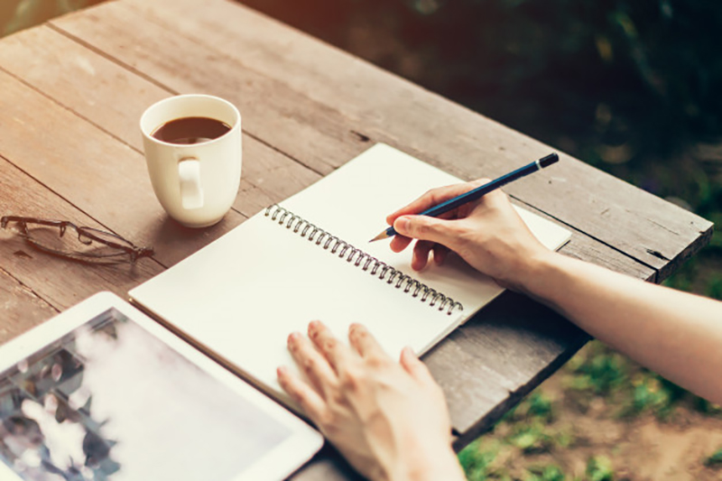 Pessoa escrevendo à lápis em um caderno com folhas brancas