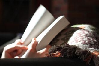Pessoa lendo livro sob o sol e debaixo das cobertas