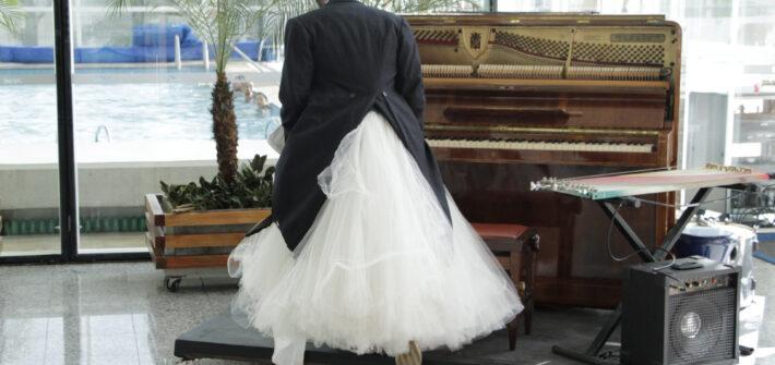 Foto homem de vestido de noiva e terno em tablado com piano e teclado