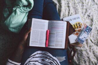 Pessoa sentada na cama lendo um livro