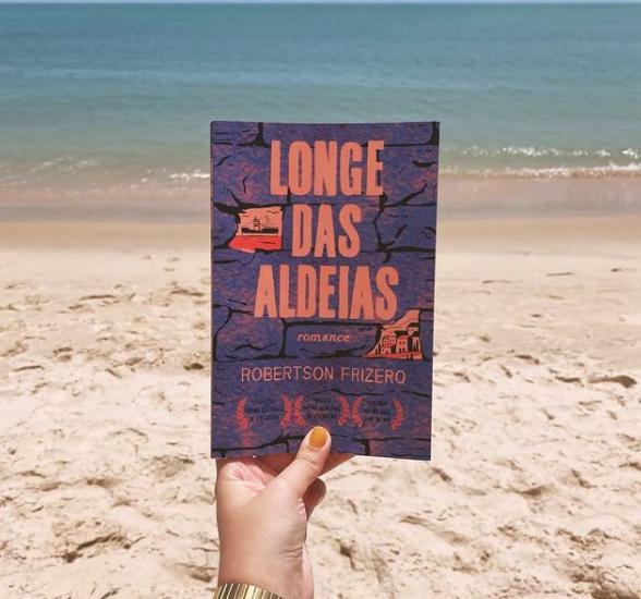 Mão feminina segurando livro Longe das Aldeias na praia
