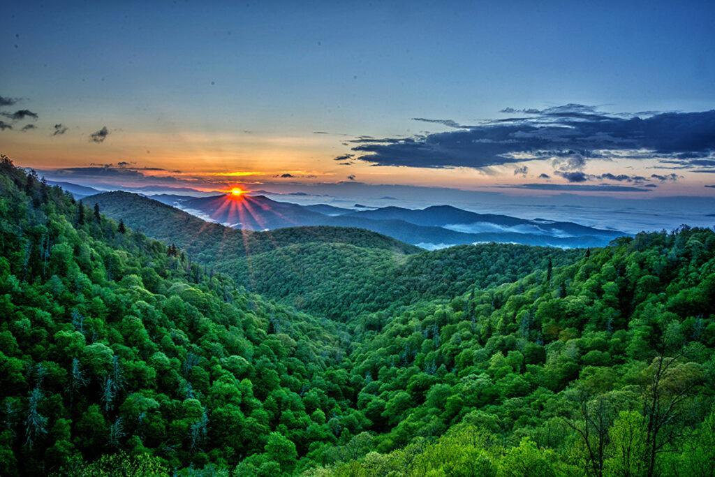 Montanhas verdejantes com sol laranja ao fundo