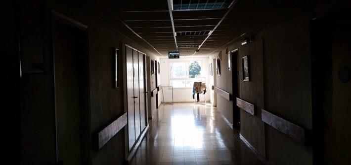 Corredor de hospítal escuro com janela ao fundo